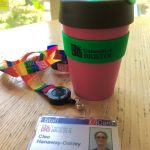 The image shows a Bristol University branded keep cup and a Bristol University lanyard and staff card